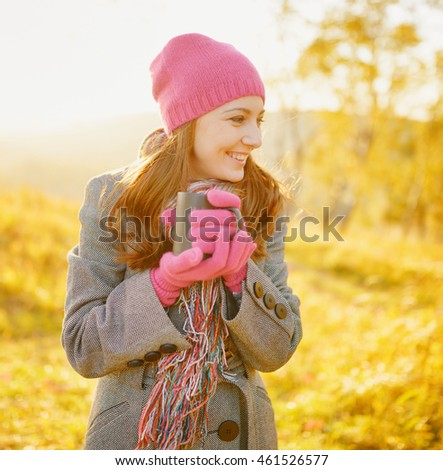 Young smiling woman with coffee mug in hands enjoying sunny day in the fall season. Woman wearing fashionable purplish-red hat and gloves on nature yellow background. Outdoor portrait in autumn.