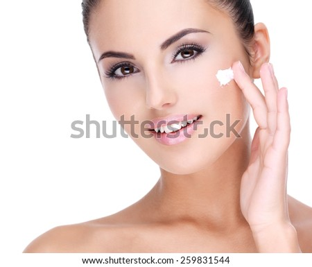 Young smiling  woman with cosmetic  cream on a pretty fresh face - isolated on white - stock photo