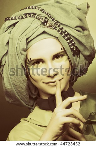 Young smiling woman with creative make-up in blue turban