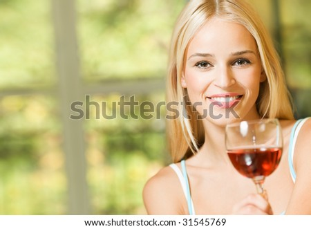 Young smiling woman with glass of red wine, indoors - stock photo