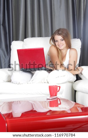 young smiling woman with laptop at home - stock photo