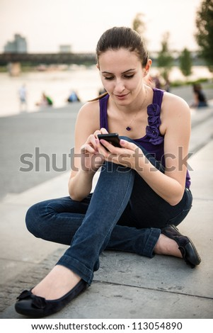 Young smiling woman with mobile phone ( touchscreen smartphone) - stock photo