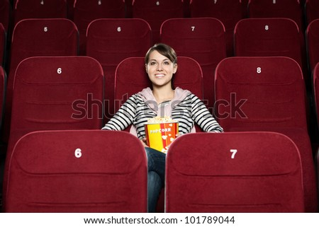 Young smiling  woman with popcorn at the cinema - stock photo