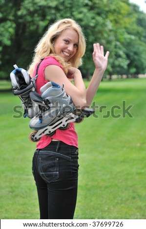 Young smiling woman with roller skates giving good bye gesture with hand. Outdoors in park.