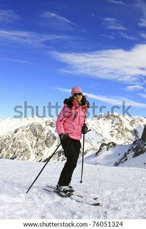 Young smiling woman with skis standing on the mountain