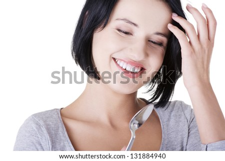 Young smiling woman with spoon (pleasure from eating), isolated on white