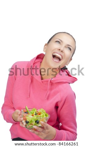 young smiling woman with vegetable salad looking up and laughing over white background - stock photo