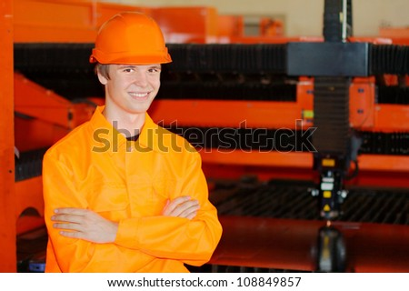 Young smiling worker with a working laser on a background