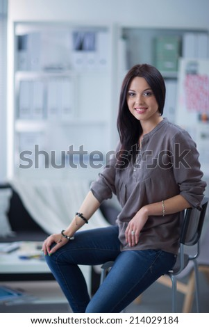 Young smilling beautiful woman sitting on couch at her room - stock photo
