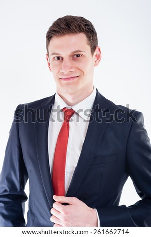 Young  smilling businessman in black suit and red tie holding his suit with the left hand - stock photo