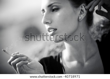 Young smoking woman. Black and white portrait. - stock photo