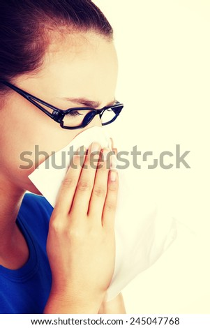 Young sneezing casual woman with tissue.  - stock photo