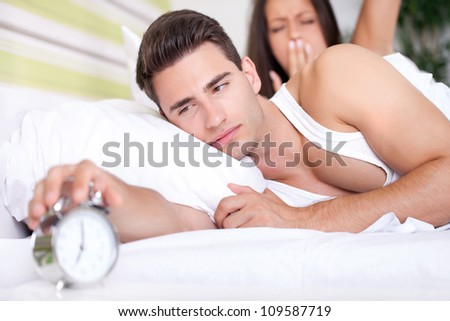 Young snoozing couple in bed waking up to alarm clock.
