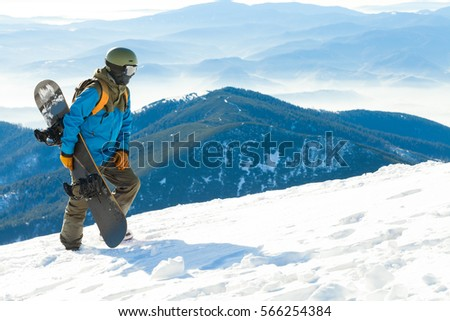 Young snowboarder in helmet walking at the very top of a mountain