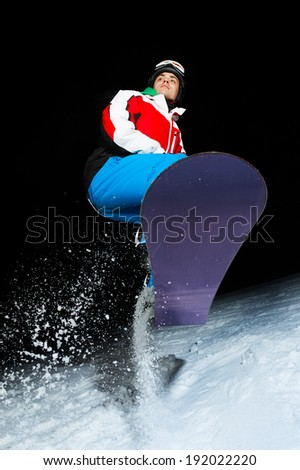 Young snowboarder jumping at night - stock photo