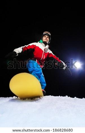 Young snowboarder ready to slide at night - stock photo