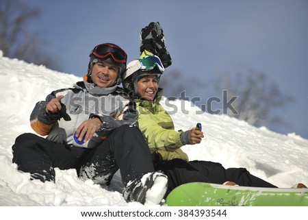 young snowboarders couple relaxing and enjoy on sunny winter day on fresh snow