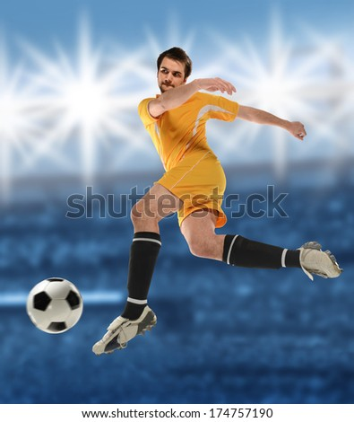Young soccer player kicking ball inside stadium