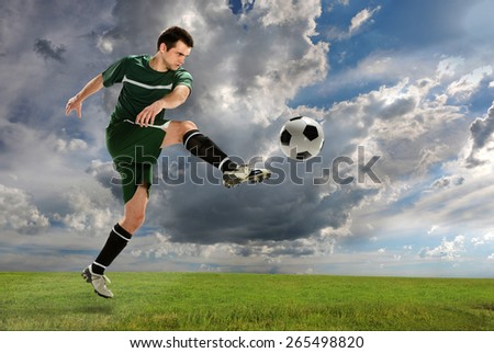 Young soccer player kicking ball outdoors - stock photo