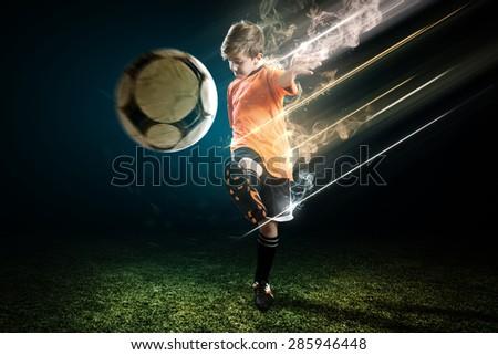 Young Soccer player kicks the ball - stock photo