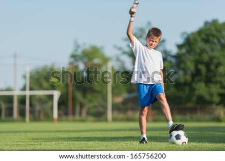 Young soccer player with his new trophy - stock photo