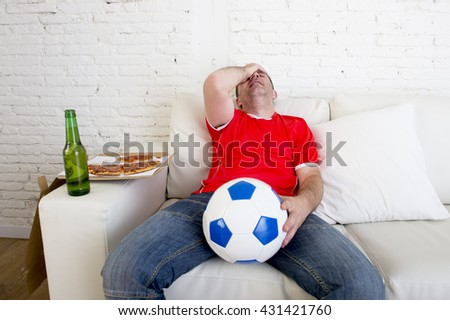 young soccer supporter man holding beer bottle watching football game on television sitting at home couch sad and disappointed for failure or defeat covering his face wearing team jersey - stock photo