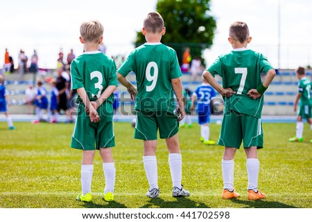 Young soccer team. Reserve players standing together and watching football soccer tournament match for youth teams. Sports background. - stock photo