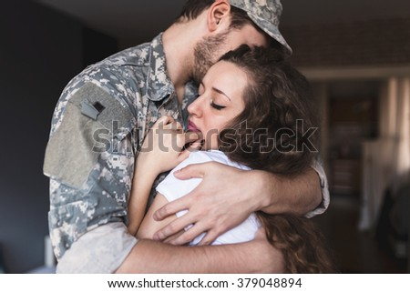 Young soldier embracing his woman. Please don't leave me again. Woman crying. Selective focus, depth of field  - stock photo
