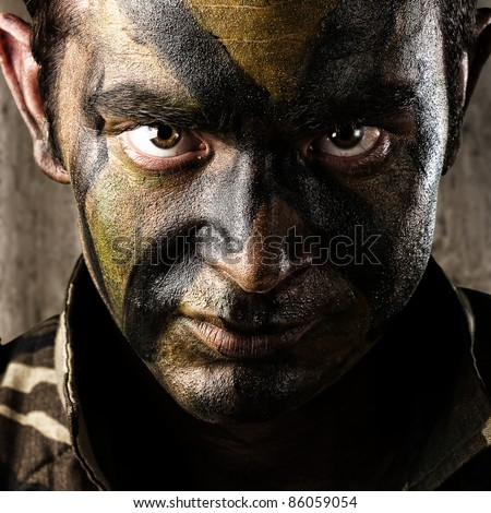 young soldier face looking straight ahead against a a grunge wall - stock photo