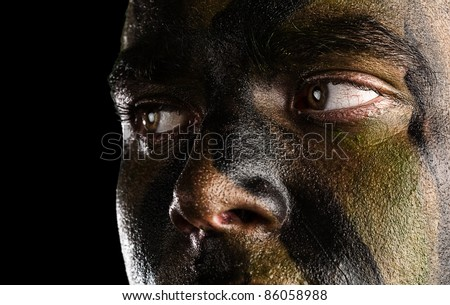 young soldier face with jungle camouflage on black background