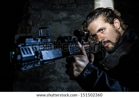 Young soldier holding gun, dressed in black, underground. Special Forces - stock photo
