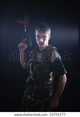 Young soldier in camouflage with kalashnikov.