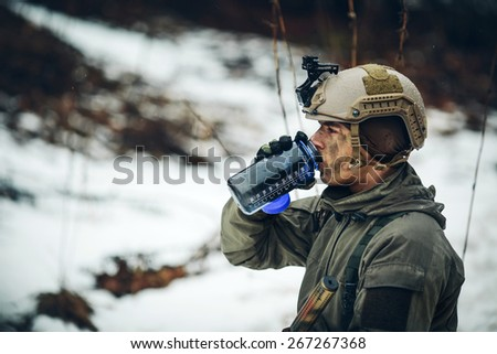 young soldier member drink water in forest