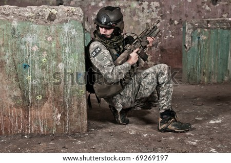 Young soldier on patrol, aiming - stock photo