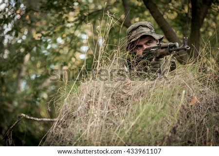 Young soldier pointing his gun from cover during training in forest