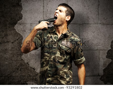 young soldier wearing a jungle camouflage committing suicide against a grunge brick wall - stock photo