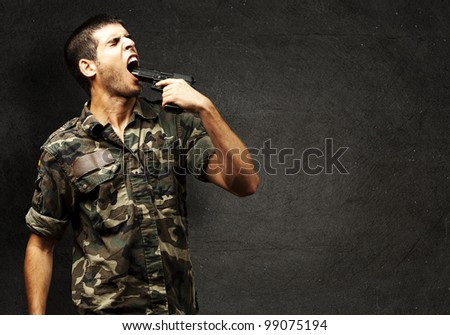 young soldier wearing a jungle camouflage committing suicide against a grunge wall - stock photo