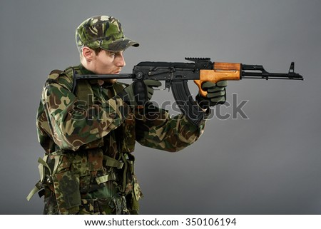 Young soldier with camouflage uniform aiming the target, studio shoot - stock photo