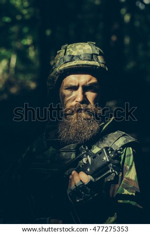 Young soldier with sad bearded face in military helmet and camouflage with gun on forest background