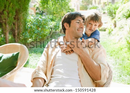 Young son hugging his father while relaxing and sitting on a chair by a house garden during a sunny day while on holiday during the summer. - stock photo