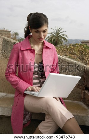 Young sophisticated woman using a laptop outdoors.