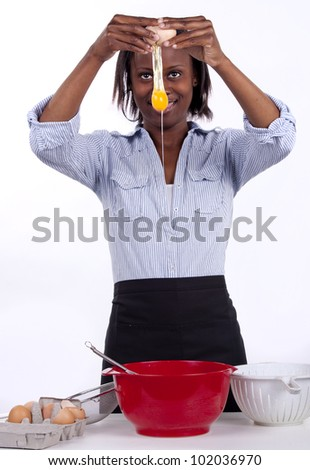 Young South African woman breaking an egg into a bowl - stock photo
