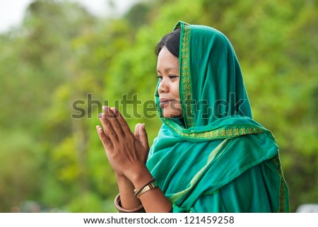 Young south-east asian woman praying with head dress - stock photo