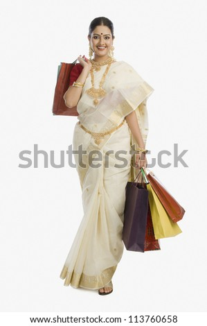 Young South Indian woman holding shopping bags and smiling - stock photo