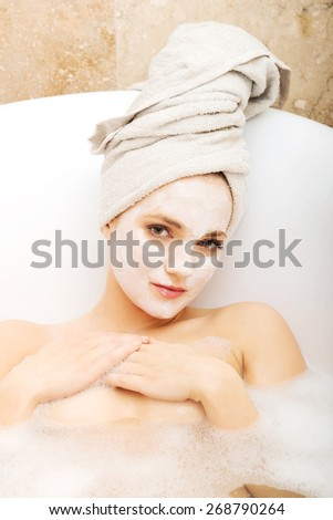 Young spa woman relaxing in bathtub with cream moisturizer.  - stock photo