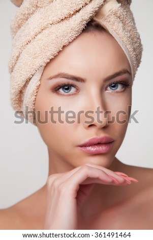 Young spa woman touching her face after beauty treatment - stock photo