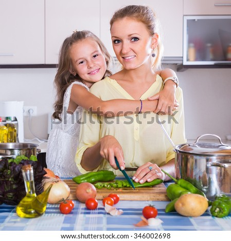 young spanish mom and little daughter cooking vegeterian dish indoors