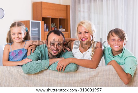 young spanish parents with two children posing in home interior