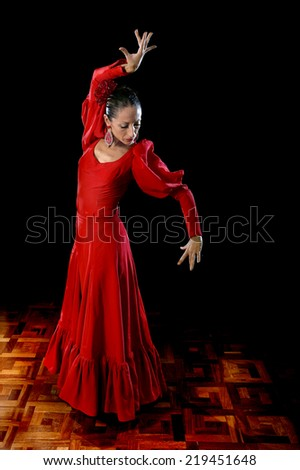 young Spanish woman dancing Sevillanas and Flamenco wearing typical folk red dress in traditional Dance of Spain concept performing show on wooden stage