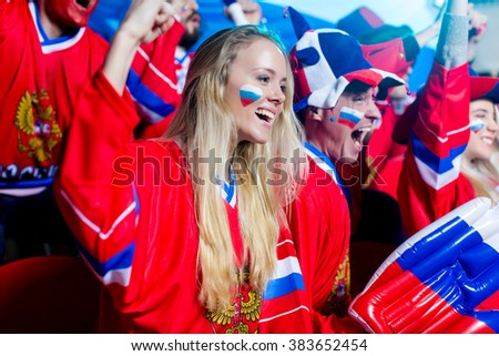 Young spectators in uniform in stadium - stock photo